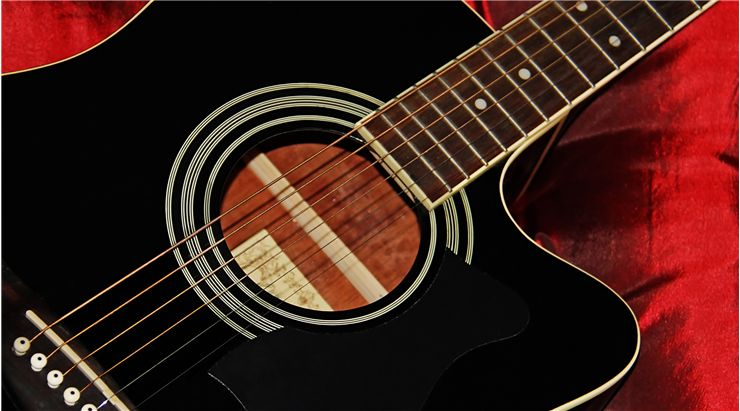 Black Acoustic Guitar on a Red Satin Background
